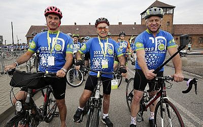Three-time Tour de France winner Greg LeMond, right, Marcel Zielinski, a Holocaust survivor, center, and Jonathan Ornstein, the director of the Jewish Community Center of Krakow, pose for the media in Oswiecim, Poland, on Friday June 29, 2018. Three-time Tour de France winner Greg LeMond, two Holocaust survivors and dozens of others took part in a symbolic ride from Auschwitz-Birkenau to a Jewish cultural center in Poland to support the renewal of Jewish life.(AP Photo/Katarzyna Bednarczyk)