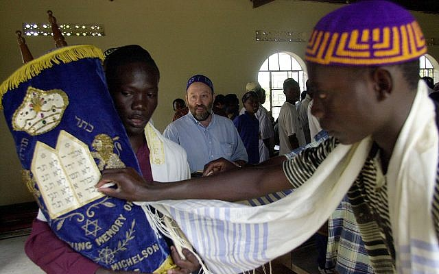 Illustrative: A Ugandan Abayudaya Jew leans forward to touch a Torah scroll carried by Enosh Keki Mainah, 23, left, during Shabbat services at the synagogue in Nabugoya, Uganda, on March 3, 2002. (AP Photo/Sayyid Azim/File)