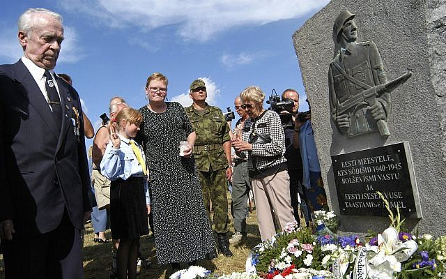 Illustrative: People stand during an unveiling ceremony of the monument to Estonian soldiers fighting alongside the Nazis against the Soviet army, in Lihula, Estonia, Friday, Aug. 20, 2004.  (AP Photo/NIPA)