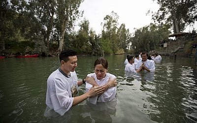 Indonesian priests baptize Christian pilgrims in the Jordan river at Yardenit baptismal site in Israel, March 17, 2017. (AP Photo/Dusan Vranic)