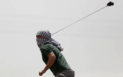 A demonstrator throws a stone at Israeli soldiers during clashes in the West Bank village of Nebi Saleh near Ramallah, April 21, 2017. (AP Photo/Majdi Mohammed)