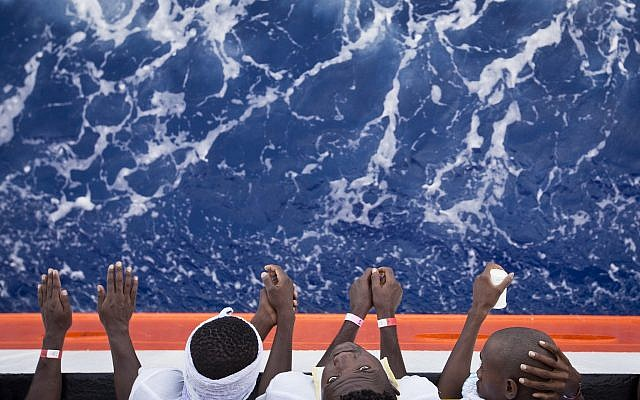 """African migrants stand on the deck of the Aquarius vessel of the """"SOS Mediterranee"""" and MSF (Doctors Without Borders) NGOs, in the Mediterranean Sea, southwest of Malta, Thursday, August 31, 2017. (AP/Darko Bandic)"""