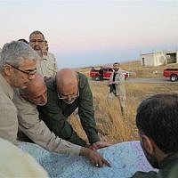 This file photo provided on Friday October 20, 2017 by the government-controlled Syrian Central Military Media shows Iran's army chief of staff Maj. Gen. Mohammad Bagheri, left, looking at a map with senior officers from the Iranian military as they visit a front line in the northern province of Aleppo, Syria. (Syrian Central Military Media, via AP)
