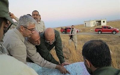 This file photo provided on October 20, 2017 by the government-controlled Syrian Central Military Media shows Iran's army chief of staff Maj. Gen. Mohammad Bagheri, left, looking at a map with senior officers from the Iranian military as they visit a front line position in the northern province of Aleppo, Syria. (Syrian Central Military Media, via AP)