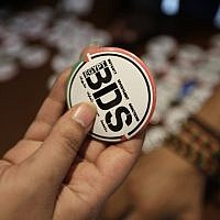 Illustrative: An Egyptian buys a pin with the Boycott, Divestment and Sanctions (BDS) logo in Cairo, Egypt, in 2015. (AP Photo/Amr Nabil)