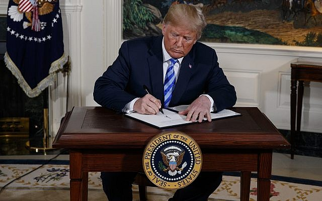 US President Donald Trump signs a Presidential Memorandum withdrawing from the Iran nuclear deal from the Diplomatic Reception Room of the White House, on May 8, 2018. (AP Photo/Evan Vucci)