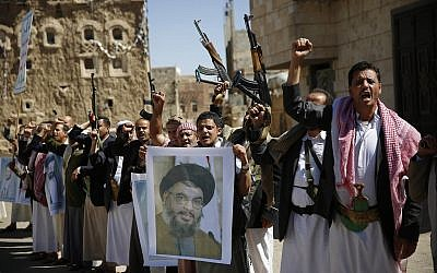 FILE - In this March 3, 2016 photo, Shiite rebels, known as Houthis, hold a poster of Hezbollah leader Sheikh Hassan Nasrallah during a rally in support of Hezbollah, in Sanaa, Yemen. (AP Photo/Hani Mohammed, File)