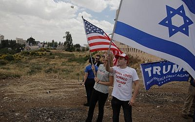 Israelis hold American and Israeli flags with the new US embassy in the background in Jerusalem, Monday, May 14, 2018. (AP Photo/Sebastian Scheiner)