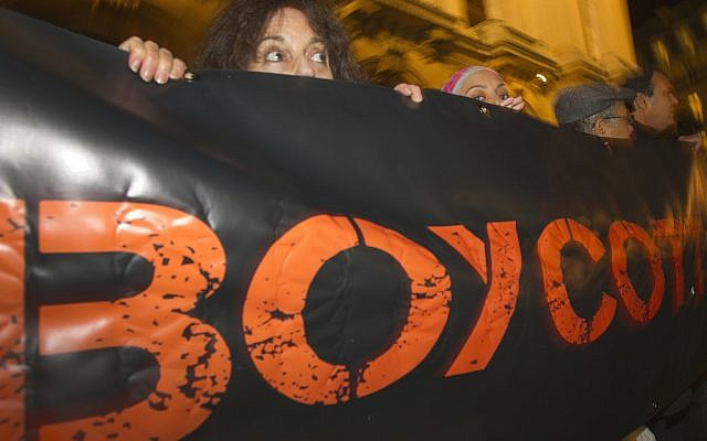 In this Oct. 31, 2012 file photo, French demonstrators and supporters of Palestinians hold a placard with the word 'Boycott' during a demonstration in Paris, France. (AP Photo/Jacques Brinon, File)