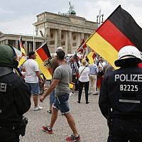 Supporters of German AfD wave flags in front of the Brandenburg Gate in Berlin, Germany, May 27, 2018. (AP Photo/Michael Sohn)