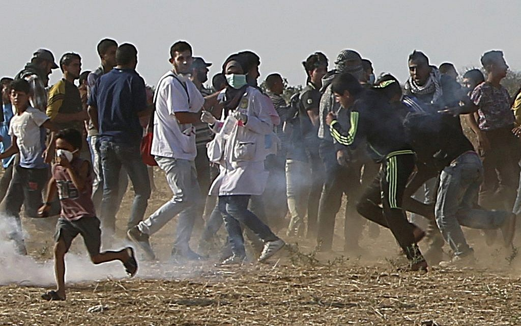 Volunteer paramedic Razan Najjar, 21, center, is seen before she was killed, running with protesters to take cover from tear gas fired by Israeli troops, in the Gaza Strip, near the border with Israel, during a violent demonstration east of Khan Younis, June 1, 2018. (AP Photo/Adel Hana)