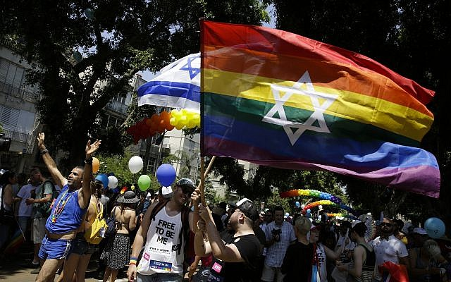 Israelis and tourists wave flags as they participate in the Gay Pride parade in Tel Aviv, Friday, June 8, 2018. (AP/Sebastian Scheiner)