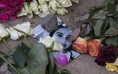 Roses cover the photo of the 14-year-old Susanna Maria Feldman killed in Wiesbaden, Germany, Friday, June 8, 2018 (Boris Roessler/dpa via AP)