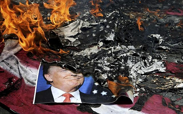 A poster of the US President Donald Trump is set on fire during the annual anti-Israeli Al-Quds, Jerusalem, Day rally in Tehran, Iran, Friday, June 8, 2018 (AP Photo/Ebrahim Noroozi)