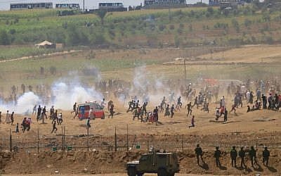 Palestinians run from tear gas fired by Israeli soldiers during clashes along the Gaza Strip border fence on June 8, 2018. (AP Photo/Ariel Schalit)