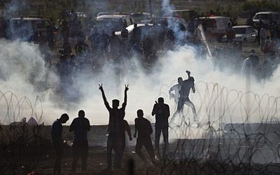 Palestinians protesters run from tear gas fired by Israeli troops on the Israel-Gaza border, Friday, June 8, 2018. (AP Photo/Ariel Schalit)