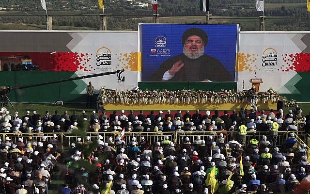 Hezbollah supporters listen to leader Hassan Nasrallah deliver a speech on a giant TV screen from a secret location, during a rally to mark al-Quds Day, at the village of Maroun el-Rass on the Lebanon-Israel border, south Lebanon, Friday, June 8, 2018 (AP Photo/Mohammed Zaatari)
