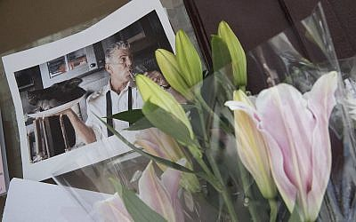 Flowers and a photo of Anthony Bourdain are seen at a make shift memorial outside the building that once housed Le Halles restaurant on Park Avenue, Friday, June 8, 2018, in New York. (AP Photo/Mary Altaffer)