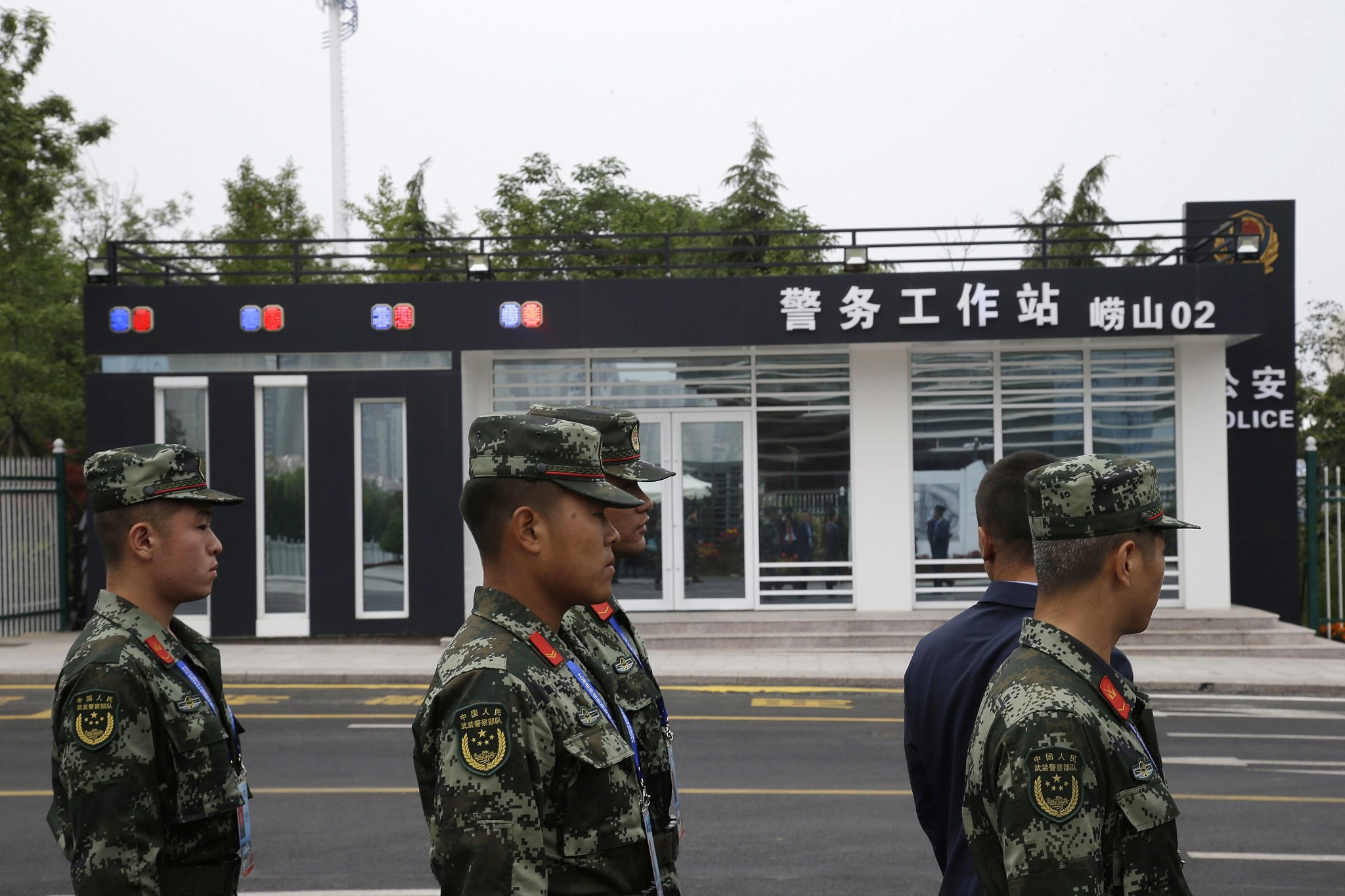 Soldiers stand guard near a police station at the Shanghai Cooperation Organization (SCO) Summit media center in Qingdao in eastern China's Shandong Province, Saturday, June 9, 2018. (AP Photo/Dake Kang)
