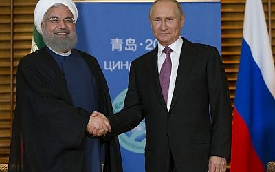 Russian President Vladimir Putin, right, and Iranian President Hassan Rouhani shake hands during their meeting in Qingdao, China, Saturday, June 9, 2018.  (AP Photo/Alexander Zemlianichenko, Pool)