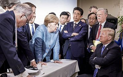 German Chancellor Angela Merkel, center, speaks with US President Donald Trump, seated at right, during the G7 Leaders Summit in La Malbaie, Quebec, Canada, on June 9, 2018. (Jesco Denzel/German Federal Government via AP)