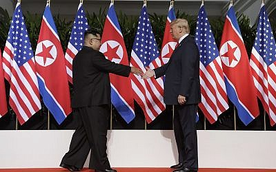 US President Donald Trump (right) reaches to shake hands with North Korea leader Kim Jong Un at the Capella resort on Sentosa Island, June 12, 2018, in Singapore. (AP Photo/Evan Vucci)