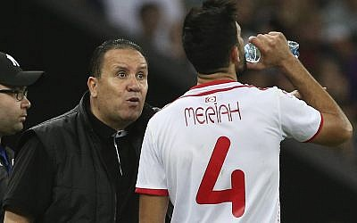 In this Saturday, June 9, 2018 file photo, Tunisia's head coach Nabil Maloul, left, speaks with Tunisia's Yassine Meriah, who drinks water during a friendly soccer match against Spain in Krasnodar, Russia. (AP Photo, File)