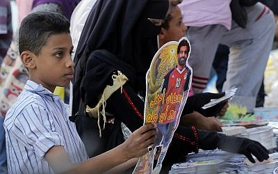 In this May 16, 2018 file photo, a boy buys a Ramadan decoration depicting the Egyptian Liverpool soccer player Mohamed Salah in Sayyeda Zeinab market in preparation for the holy month of Ramadan, in Cairo, Egypt. (AP Photo/Amr Nabil, File)