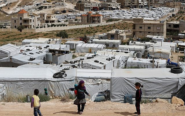 Syrian refugee children play at an informal refugee camp, which is seen set between the houses and buildings in Arsal, near the border with Syria, east Lebanon, Wednesday, June 13, 2018 (AP Photo/Hussein Malla)