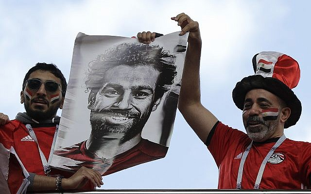 Egyptian supporters lift a photo of national soccer team player Mohamed Salah ahead the group A match between Egypt and Uruguay at the 2018 soccer World Cup in the Yekaterinburg Arena in Yekaterinburg, Russia, Friday, June 15, 2018. (AP Photo/Mark Baker)