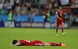 Iran's Sardar Azmoun lies flat out on the ground after the end of the group B match between Iran and Spain at the 2018 soccer World Cup in the Kazan Arena in Kazan, Russia, Wednesday, June 20, 2018. (AP/Sergei Grits)