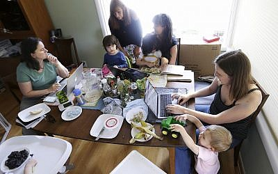 In this Wednesday, June 27, 2018, photo, a small group of stay-at-home mothers, with children at their sides, work to organize an immigration rally in Portland, Oregon. From left to right are Kate Sharaf, Lisa Carol Stiller, Erin Conroy and Caely Barrett. (AP Photo/Don Ryan)