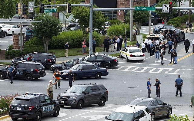 Maryland police officers block the intersection at the building entrance, after multiple people were shot at a newspaper in Annapolis, Md., June 28, 2018. (AP Photo/Jose Luis Magana)