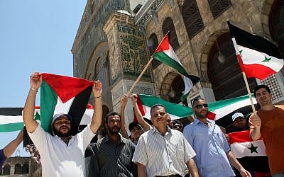 Syrians and Palestinians wave their flags during a festival held inside the Umayyad Mosque in Damascus, Syria on Friday, Aug. 2, 2013 to commemorate Al-Quds (Jerusalem) Day. (AP Photo)