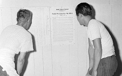 Interned Japanese men read US President Franklin Roosevelt's proclamation on their internment, posted on the wall at Rohwer Relocation Center near McGehee, Arkansas, September 21, 1942. (AP Photo/Horace Cort)