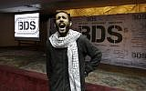 An Egyptian man shouts anti-Israeli slogans in front of banners with the Boycott, Divestment and Sanctions (BDS) logo during the launch of an Egyptian campaign that urges boycott, divestment and sanctions against Israel and Israeli-made goods, at the Egyptian Journalists' Syndicate in Cairo, April 20, 2015 (AP Photo/Amr Nabil, File)