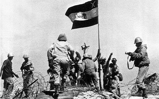 Egyptian troops jubilate as they plant their flag atop a bunker on Bar-Lev line east of Suez Canal, October 13, 1973. (AP Photo/Pool/Ahmed Tayeb)