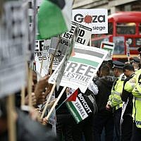 Illustrative: A policeman looks down a line of demonstrators near the Israeli embassy protesting against the action taken against Gaza, in London, Friday, July 11, 2014. (AP/Alastair Grant)