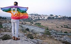 An Israeli teen wrapped in a Gay Pride flag near the settlement of Efrat, June 3, 2018. (Jacob Magid/Times of Israel)