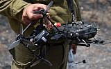An IDF operator holds up his drone and remote control on June 7, 2018, in a field burned by 'fire kites' from the Gaza Strip. (Judah Ari Gross/Times of Israel)