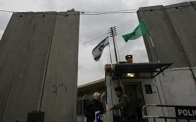 An illustrative photo of a Border Police officer checking the ID of a Palestinian woman at the security barrier next to the West Bank village of Abu Dis on February 25, 2008. (Kobi Gideon/Flash90)