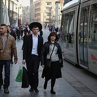 A young Israeli secular couple walks next to an ultra-Orthodox couple as the light rail goes by on Jaffa road in central Jerusalem on January 22, 2014. (Hadas Parush/Flash 90)