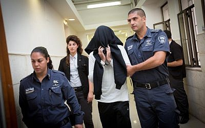 Border Police officer Ben Deri, who was later convicted of killing a 17-year-old Palestinian teenager during riots in the West Bank town of Betunia in 2014, covers his face as he walks into a hearing at the Jerusalem District Court on December 7, 2014. (Miriam Alster/Flash90)