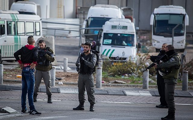 Israeli security forces check a Palestinian man at the entrance to the Shuafat Refugee Camp in East Jerusalem on December 2, 2015.  (Hadas Parush/Flash90)