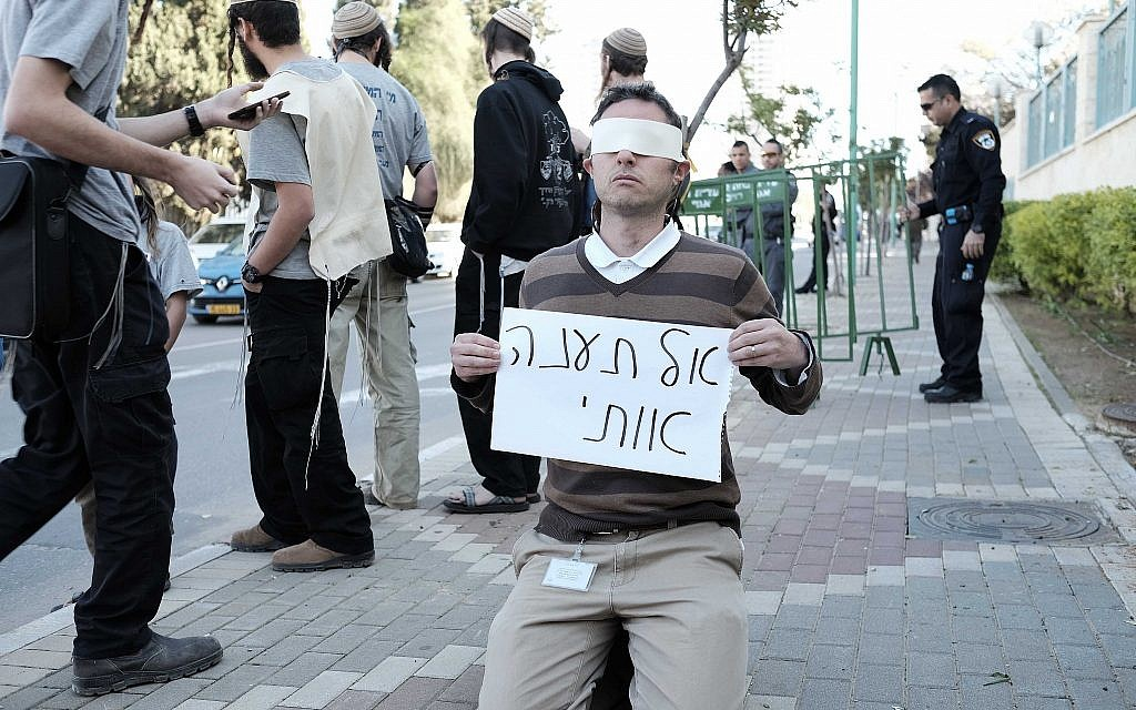 "Illustrative: A right-wing Jewish activist holds a sign reading, ""Do not torture me"" outside the Duma terror attack trial in Petah Tikva on December 28, 2015. (Tomer Neuberg/Flash90)"