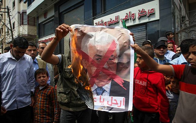 Palestinians burn a poster of Palestinian Authority President Mahmoud Abbas during a protest against Israel and the PA in Khan Younis in the southern Gaza Strip on April 14, 2017. (Abed Rahim Khatib/Flash90)