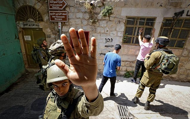 An Israeli soldier attempting to block the view of a photographer as troops search Palestinian men in the West Bank city of Hebron on June 22, 2017. (Wisam Hashlamoun/Flash90)