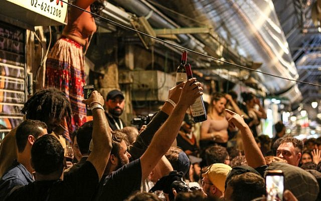 People seen partying at a bar in the Mahane Yehuda market in Jerusalem, on May 8, 2018. (Liba Farkash/Flash90)