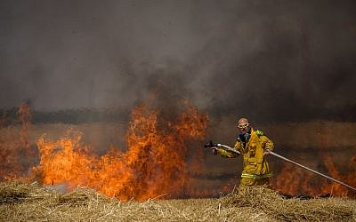 Israeli firefighters extinguish a fire in a wheat field caused from kites flown by Palestinians, near the border with the Gaza Strip, May 30, 2018. (Yonatan Sindel/Flash90)