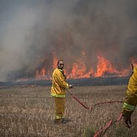 File: Israeli firefighters extinguish a fire in a field in southern Israel, caused by kites flown by Palestinians from the Gaza Strip on June 5, 2018. (Yonatan Sindel/Flash90)